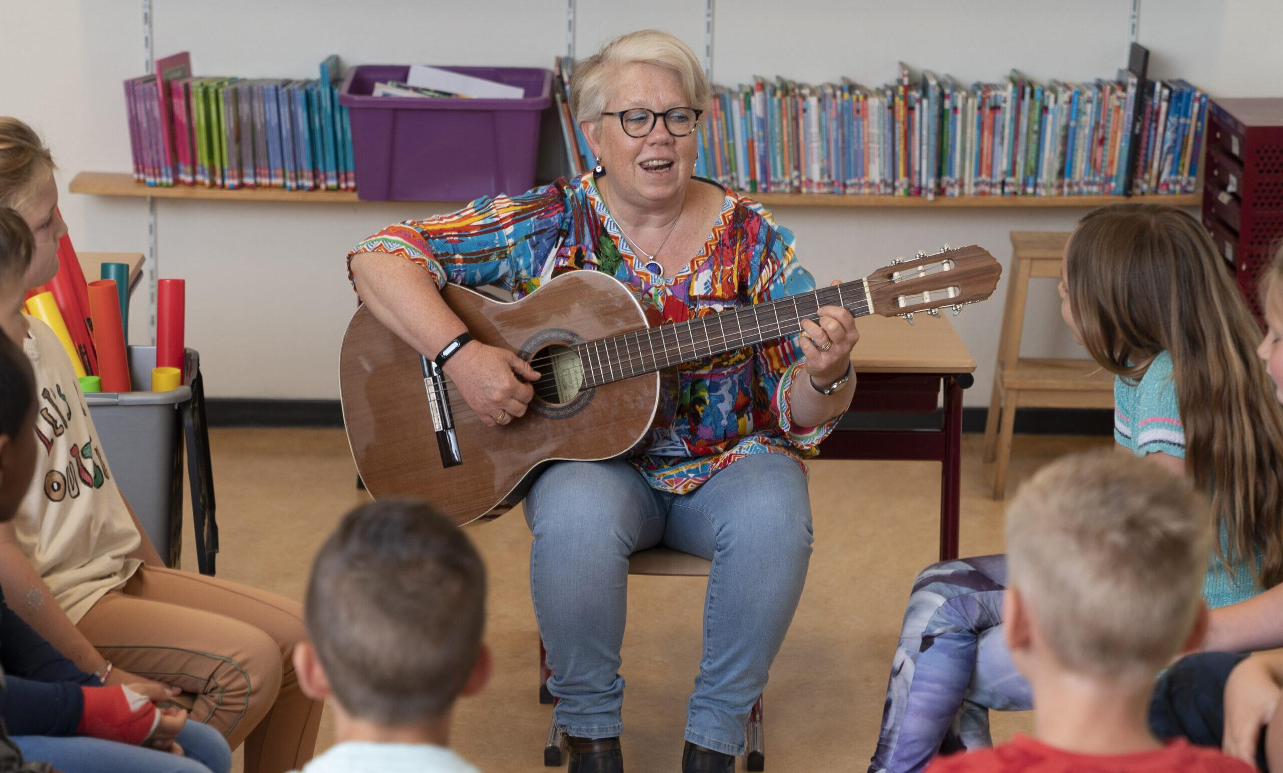 vrouw speelt gitaar in een kring met kinderen