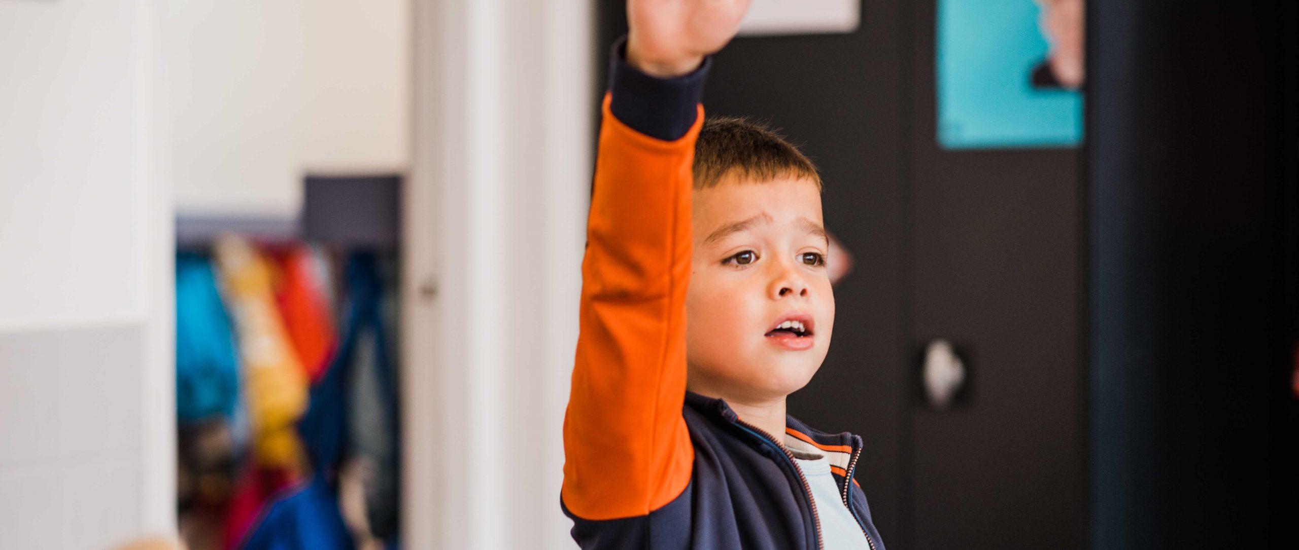 schoolkind steekt hand op