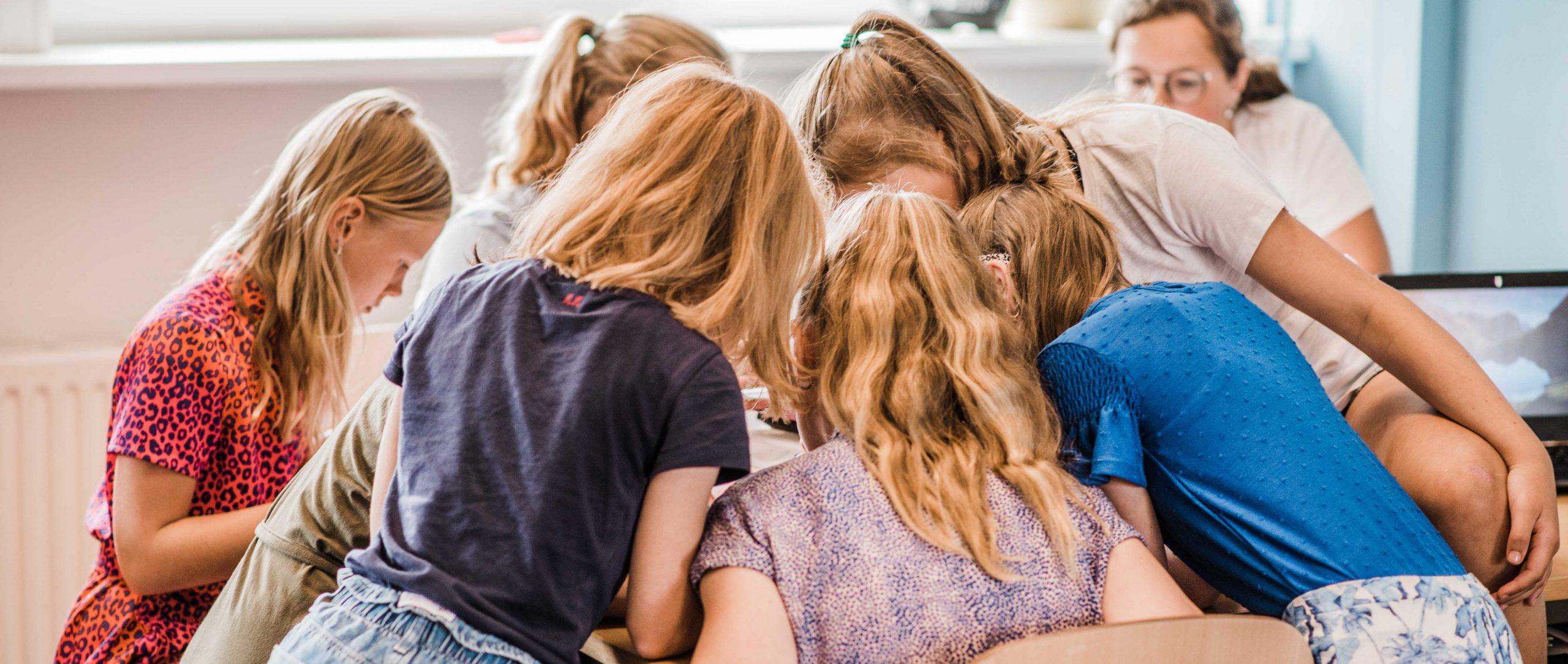 zes schoolkinderen kijken naar een boek