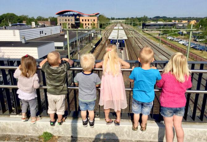 kinderen kijken naar het spoor vanaf een brug